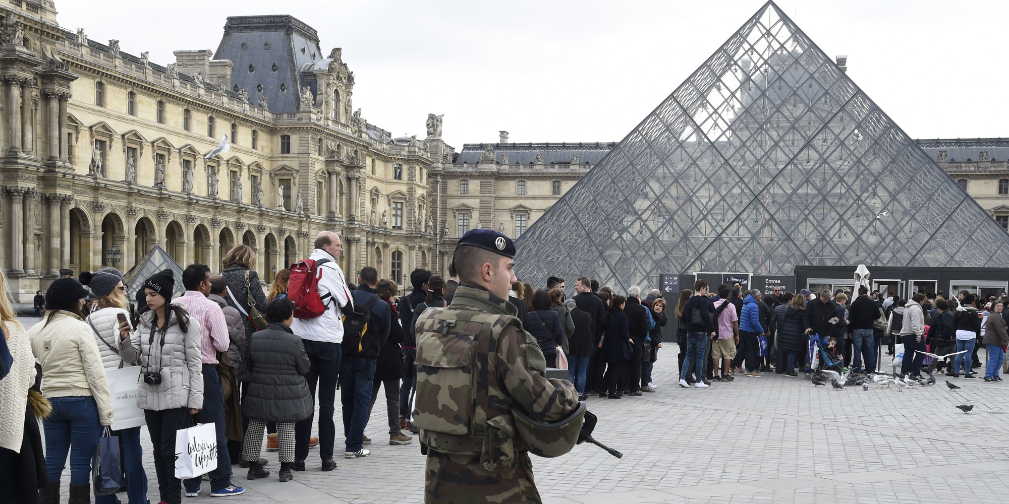 A French soldier enforcing the Vigipirate plan, France's national security alert system, patrols in front of the Louvre museum as visitors line up for entry the day of its reopening on November 16, 2015 in Paris, three days after a series of deadly coordinated attacks claimed by Islamic State jihadists, which killed at least 129 people and left more than 350 injured on November 13. AFP PHOTO/DOMINIQUE FAGET